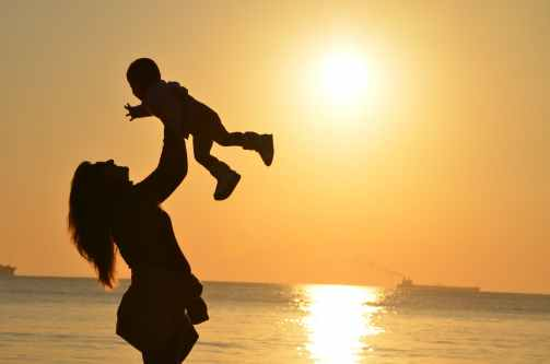 Mother and baby by the sea sunset